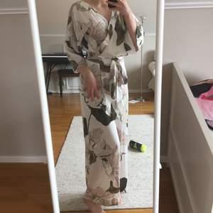 sååå vacker byxdress! elegant, perfekt plagg för finare tillfällen. flowigt material med blommönster och fåglar, påminner mycket om en kimono. stängs med dragkedja bak och har halvöppen rygg. kan knytas fram och bak. endast använd en gång så i nyskick!