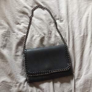 Säljer denna svarta axelremsväska. Jag har själv gjort den till en axelremsväska (Se bild 2) men det går såklart att göra bandet långt igen om man vill det. Nypris 150kr, säljer den för 50kr+ frakt.