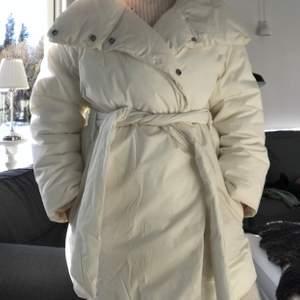 Vit supersnygg jacka från H&M med bälte i midjan, knappt använd. Frakt ingår ej😇