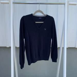 En v-ringad tunnstickad tröja ifrån GANT i en marinblå färg och med ett vitt broderat märke på vänster bröst. Endast använd en gång och är i nyskick. (Material: 80% ull och 20% polyamid)