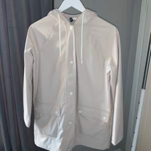 Ljus Regnjacka från H&M som jag köpte för ungefär 1 år sedan. Bara använd en gång. Jackan stängs med knappar.