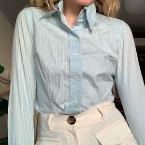 En blå randig skjorta med speciell krage, extra spetsig. Superskön och sitter tight. Så fin!