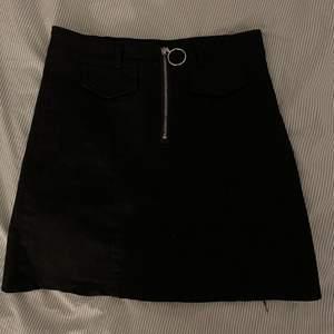 Superfin svart tygkjol med en dragkedja i fram. Passar xs/s