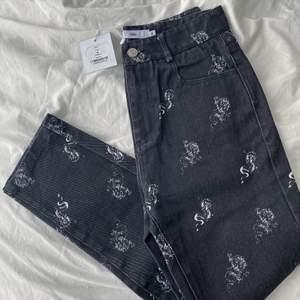 Helt nya raka svarta/mörkgråa jeans med drakar på från Adika🤍 jeansen är köpta i newyork för ca 2 år sedan men aldrig kommit till användning då de är försmå för mig. De är köpta för 52$. Skicka privat vid frågor, intresse eller för exakta mått🤍