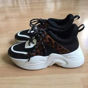 Platå sneakers med leopardmönstrade detaljer. Sluttande platåsula, högsta höjd ca 7cm. Helt veganska, material är bla skinnimitation. Använd bra några få gånger så de är i jättefint skick!