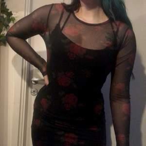 Två klänningar i en: svart enkel underklänning som går att ha för sig, och en meshklänning med röda rosor ovanpå. Endast provad.