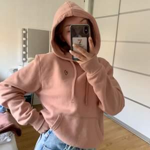 Säljer nu min rosa hoodie från H&M. Jättebekväm och mysig! Ficka på magen och fungerande snören till luvan. Det finns även ett broderat svart hjärta på vänster sida.