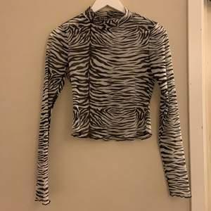 Säljer min croppade zebra mesh tröja från Gina tricot💕 tröjan har en liten krage med krusad kant på ärmarna och vid bottnen! Köparen står för frakt!