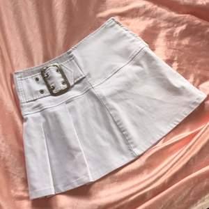 Vit supertrendig kjol med snygga detaljer. Ungefär 68-70cm midja, 34cm i längd. Obs en superelitenfläck nära ett av vecken