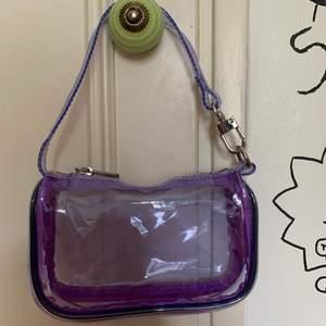Supersöt lila genomskinlig minibag från Urban outfitters! Har aldrig kommit till användning tyvärr. Säljer för 50kr + frakt💜