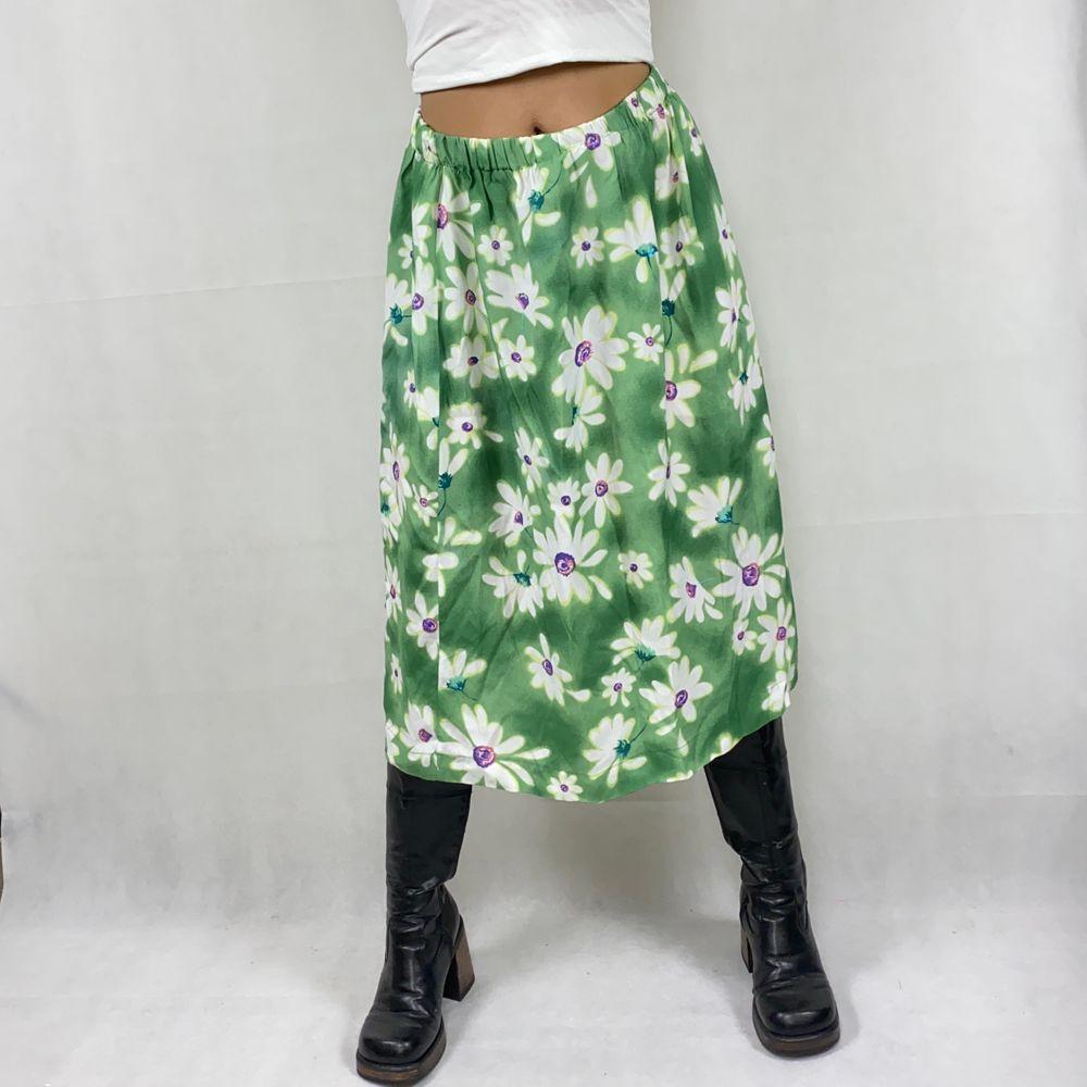 Supersöt och unik thrift flip mid kjol med grönt, blommigt material. I toppenskick! Bandet är elastiskt, sytt lite vridet så på insidan av bandet vrids ett varv runt, syns på sista bilden. En fläck finns men är nästa så den ser ut att vara en del av printet. Det finns ingen underkjol. Modellen använder storlek S och  är 169cm. Kolla gärna måtten nedanför. Midje bredd (mätt medan kjolen ligger ner utan att töjas ut) 40cm och längd 74cm. Ingen retur eller refund.  Spårbar frakt på 66kr är inräknad i priset och SafePay tar 10% av betalningen. Tyvärr kostar det lite extra då jag alltid kommer skicka spårbart och använda SafePay för bådas säkerhet. Kjolar.