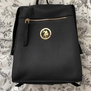En helt oanvänd svart ryggsäck med gulddetsljer från Polo. Jätte lätt och mycket utrymme för massor. Rekommenderar starkt!!!
