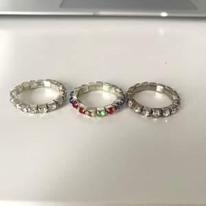 Tre ringar med stenar. En med färgade stenar och två med silverstenar. Den ena  är helt silverfärgad och den andra har lite guld mellan stenarna (se bild 2). Ringarna är 17mm men töjbara så passar även större. Inte åkte silver. Köparen står för frakt.