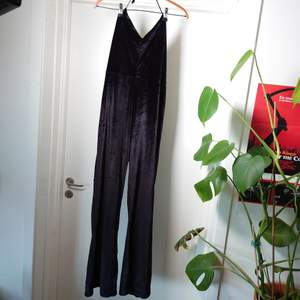En svart byxdress i krossat sammet/velour! Väldigt fin förutom snöret som är slitet, man sätter det runt halsen. Går att använda men kanske kan bytas till ett finare. Dragkedja i sidan🌻