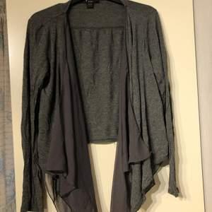 grå kofta med volanger i genomskinligt tyg. storlek M. Använd men fint skick