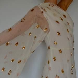 SÅ fin maxiklänning i gräddvit färg med guldiga paljettstjärnor till detaljer. Från Gina Tricot x Maja Nilsson Lindelöf - The Maria Dress. HELT NY, PRISLAPP KVAR, OANVÄND. Skriv för fler bilder! Köpt för 1499kr. GRATIS FRAKT!