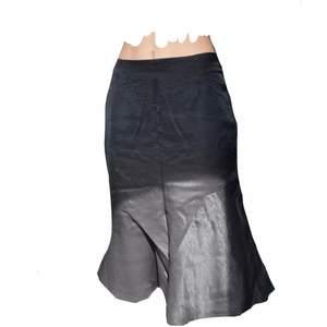 En svart sidenkjol i nyskick med en asymmetris volang längs botten. Kjolen är knälång och den är fin både lowrise och highrise. Fri frakt!❤️