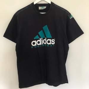 Vintage Adidas Equipment t-shirt från 90-talet. Storlek Medium och passar TTS. Har en logga på vänstra armen som man kan se på sista bilden. Vintage  skick och har inga defekter.