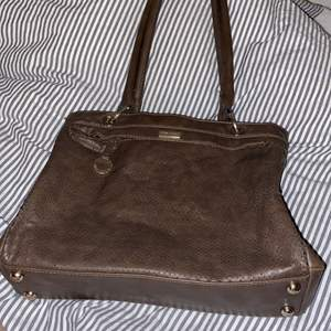 Säljer denna fina bruna handväskan. Har använts några gånger men är i bra skick. Rymlig och har en ficka med dragkedja🌸🌸