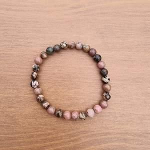 Armband med 6 mm stora kristallpärlor av rodonit.  Rundslipade stenar trädda på elastisk tråd. Ca 16 cm omkrets. Skickas i vadderat kuvert via postnord.