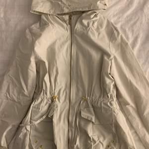 Sjukt fin regnjacka i en vanilj vit färg, nästan aldrig använd!! Den har spets vid luvan och vid armarna, man kan vika upp ärmen. Tror den kosta cirka 399kr men jag säljer den för 100kr + frakt