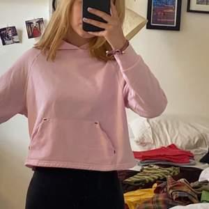 """Ljusrosa träningshoodie med små svarta detaljer på fickan och """"sportswear"""" text på ärmen. Kort men nt alls liten i storlek, köpte för typ två år sen men den passar fortfarande. Använd en gång."""
