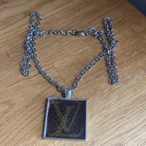 Custom made LV halsband gjort av skinn från en äkta LV-väska. Fäst på en silverfärgad kedja