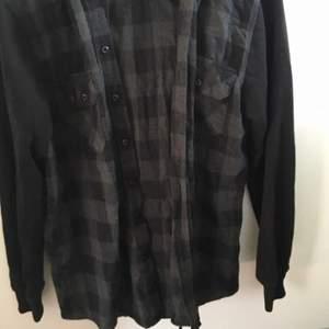 En flannel luvtröja med svarta ärmar och luva i samma material som hoodies brukar vara! Svarta knappar för att stänga den och två användbara fickor på bröstet med en knapp var. 150kr men går att diskutera!