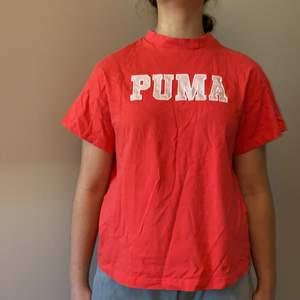 Korall färgad Puma t-shirt med märke både fram och bak. Modellen är 160.