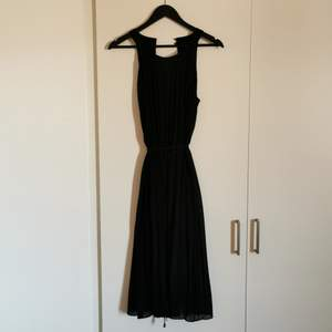A beautiful black dress with 2 buttons in the back and a band to tie it in the waist. Very comfy and flowy with a black under dress too. Never worn. From Ilse Jaksobsen.
