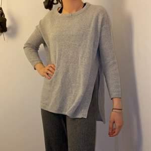 Stilren och modern stickad tröja, i en ljusgrå färg! Tröjan har en cool slit på båda sidor och den bakre delen är lite längre! Storlek XS/S!