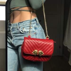"""Röd väska i fuskläder från Zara. Kommer med ett långt rött axelband, en kortare guldig kedja samt ett """"skärp"""" så du kan använda väskan som midjeväska. Knappt använd, i nyskick. Frakt ingår ej."""