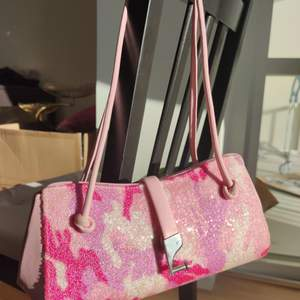 En jättegullig och fin rosa axelväska som har en unik design. Den är läder överallt förutom framsidan som är gjord av strass. Den är använd bara en gång så den är som ny. Skriv om ni vill ha fler bilder🥰