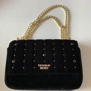 Svart väska i sammet från Victoria's Secret. Axelbandet går att justera så man kan ha det kortare (typ i midjehöjd) och längre (typ rumphöjd). Väskan har ett innerfack och ett fack på baksidan. Väskan är aldrig använd. Köparen står för frakten🌸