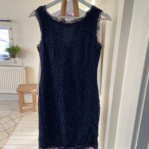 Mörkblå klänning i spets med dragkedja på baksidan