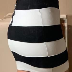 En oanvänd svart/vit kjol med dragkedja där bak.