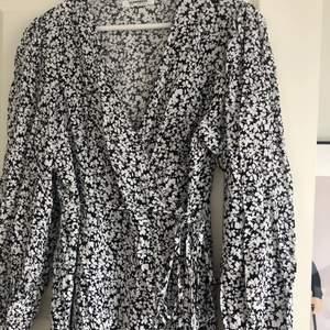 En fin omlottklänning med ballongärmar och ett fint blommönster från Glamorous i storlek 40 men passar en med storlek 36-38. Jättefin nu i sommar och använd fåtal gånger. Köparen står för frakten.