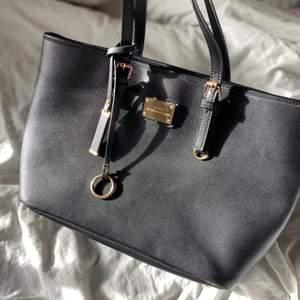 New York Portable Designs väska som är svart med guldiga detaljer.Väskan har dragkedja och inuti ett litet fack med dragkedja och sedan 2 andra små fack . Den har en liten skada som jag visar på en av bilderna men inget som syns vid användning. Köpt för 500kr, köparen betalar för frakten
