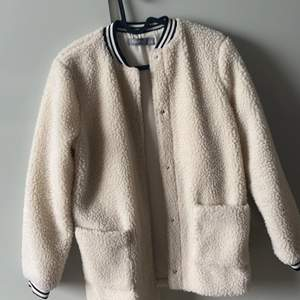 En fake ull jacka ifrån Åhléns. Aldrig kommit till användning- för liten. Två stora fickor mer mjuk ull. Stängs genom knappar.  Rekommenderas till hösten!!