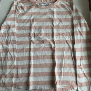 Vit och rosa randig långärmad tröja. Stl S från lager 157. Mjukt och skönt material. Tröjan kostar 20 kr, frakt ingår ej. Swipe för fler bilder.