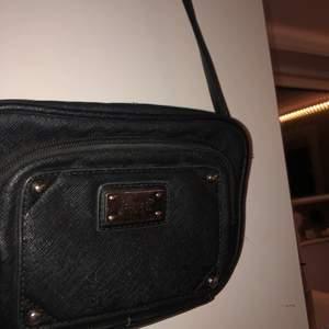 En svart Feel Axel väska. 1 ficka på baksidan och framsidan och 1 extra fick på insidan. Insidan har vitt leopardmönster och på utsidan är det Läder.