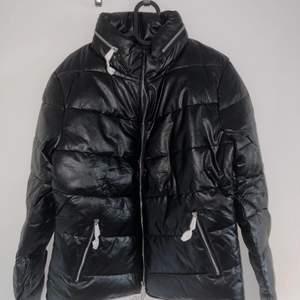Oanvänd svart pufferjacka från Parisian Tall med högkrage. Silvriga dragkedjor. Huva som kan gömmas i i ficka med dragkedja. (Skrynklig för att den har suttit ihopvikt i sin påse)  hör av er för fler bilder!