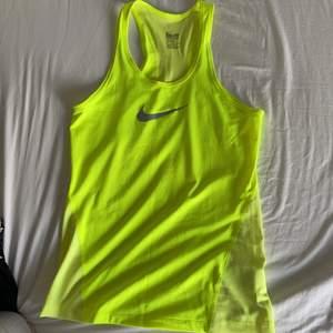 Ett nästan helt oanvänt neongult träningstimmar från Nike.         Säljer pågrund av att det är för stort för mig.              STORLEK M