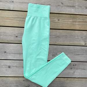 Mintgröna träningstajts av okänt märke. Sparsamt använda och i fint skick. Står ingen strl men uppskattar dom till strl S/M. Stechigt, mjukt seamless material.