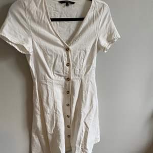 Fin vit klänning i linneliknande material med fina knappar. Har tyvärr blivit för liten för mig så den behöver ett nytt hem. Endast använd en handfull gånger så i väldigt bra skick.