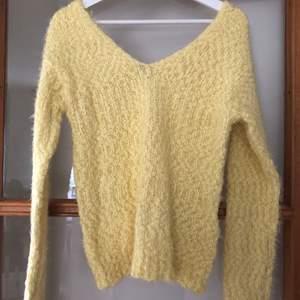 Gul stickad tröja med urringning både bak och fram, från Nelly Trend. Storlek S.