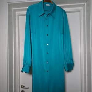 Så fin klänning/tunika i fantastisk turkos färg. Knyts i midjan eller has