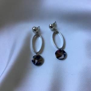 Ett par riktigt snygga örhängen som dessvärre inte kommit till användning. Blåmelerad akryl längst ner.