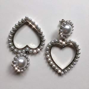 Silverfärgade örhängen i form av hjärtan. Ca 5cm stora 💕 Frakt ingår :)