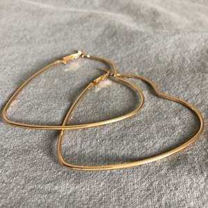 Guldiga hjärtörhängen, helt nya! Köparen står för frakten (11kr). Har ni några frågor är det bara att höra av sig! :)